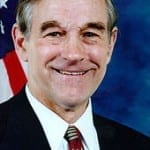Ron Paul smiling in front of an American Flag