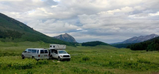 an example image for our article, showing a van and truck camper parked in a large field, surrounded by mountains outside of Crested Butte, Colorado