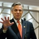 Jon Huntsman doing a gesture like he's going to palm a basketball, at a podium