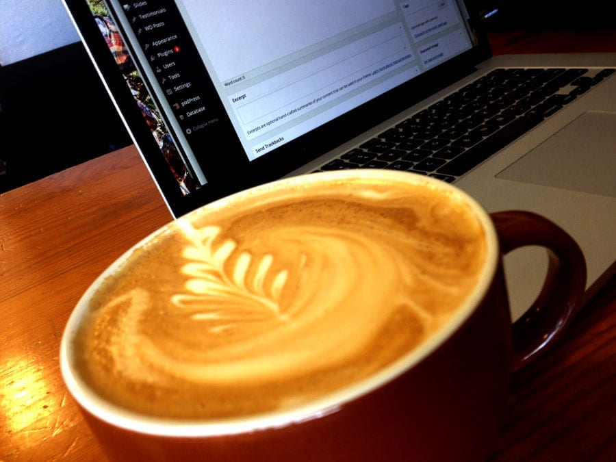 latte art, in a brown cup, a MacBook Pro in the background